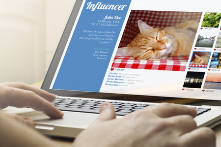 influencer: online business and influencer marketing concept: man using a laptop with influencer profile on the screen. Screen graphics are made up. Stock Photo