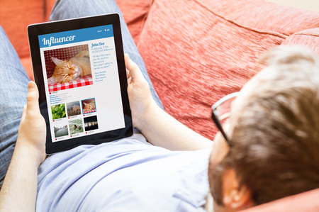 influencer: technology lifestyle and influencer marketing online concept: hipster on the sofa with online influencer marketing tablet. Screen graphics are made up.