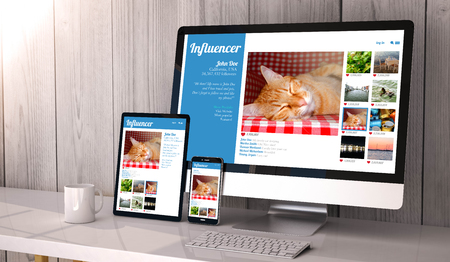 Digital generated devices on desktop, with responsive design influencer marketing profile  on screen. All screen graphics are made up. Stockfoto
