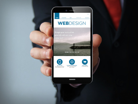 web screen: mobile design concept: businessman hand holding a 3d generated touch phone with web design site on the screen. Screen graphics are made up. Stock Photo