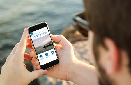 communicatie: Man aan de kust met behulp van zijn smartphone met webdesign website. Alle schermafbeeldingen zijn opgebouwd.