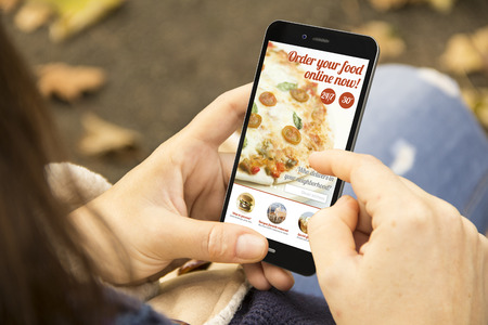shop online: order food concept: woman holding a 3d generated smartphone ordering fast food. Graphics on screen are made up. Stock Photo