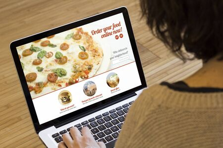 ordering: ordering food online concept: woman with a laptop showing fast food website on screen. Screen graphics are made up.