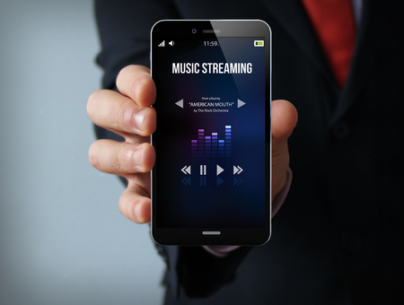 screen: new technologies delivery concept: businessman hand holding a 3d generated touch phone with music streaming app on the screen. Screen graphics are made up.