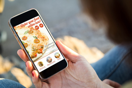 close-up view of young woman checking her mobile phone to order online. All screen graphics are made up.