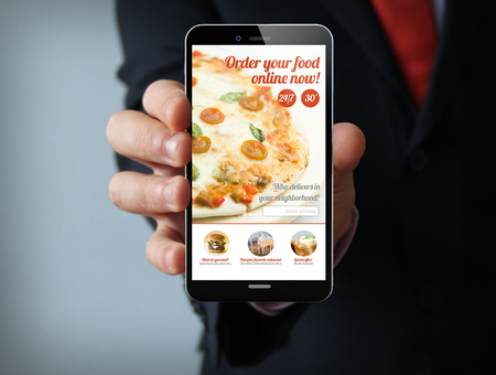 order: new technologies delivery concept: businessman hand holding a 3d generated touch phone with order online fast food website on the screen. Screen graphics are made up. Stock Photo