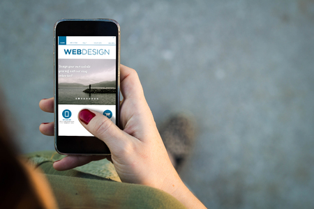 mobile phone screen: Top view of woman walking in the street using her mobile phone on a web design site with copy space. All screen graphics are made up. Stock Photo