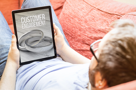 strategic advantage: technology lifestyle concept: hipster on the sofa with customer engagement tablet. Screen graphics are made up. Stock Photo