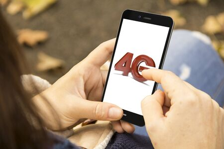 4g: connectivity concept: woman holding a 3d generated smartphone with 4g on the screen. Graphics on screen are made up. Stock Photo