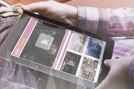 close-up view of man holding a tablet showing video marketing streaming site. All screen graphics are made up. Stock Photo