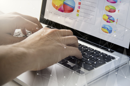 technology and business concept: man using a laptop with financial software on the screen
