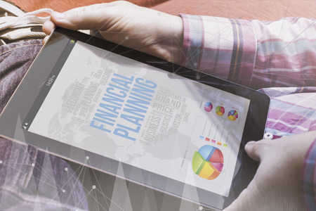 techie: close-up view of man holding a tablet showing financial planning. Financial concept. All screen graphics are made up. Stock Photo