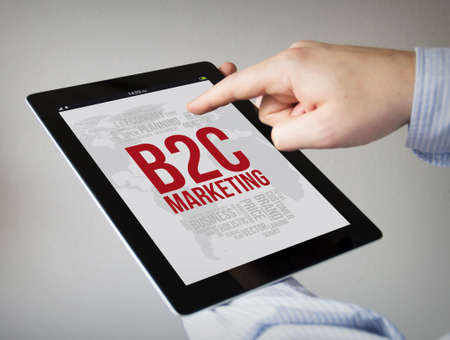 b2c: new technologies concept: hands with touchscreen tablet with b2c marketing concept on the screen. Screen graphics are made up.