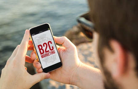 b2c: man on the coast using his smartphone with b2c marketing on screen. All screen graphics are made up. Stock Photo