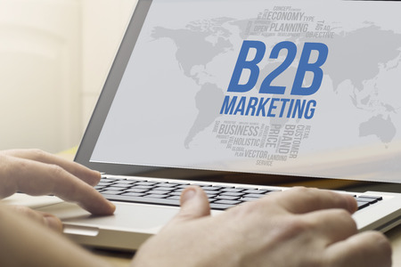 b2c: online business concept: man using a laptop with b2c marketing on the screen. Screen graphics are made up. Stock Photo
