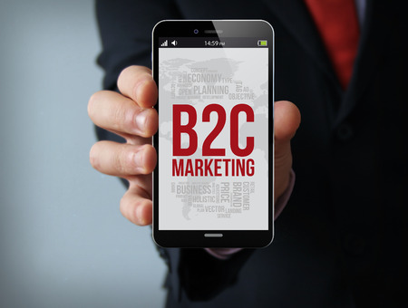 b2c: new technologies and marketing concept: businessman hand holding a 3d generated touch phone with b2c marketing on the screen. Screen graphics are made up.