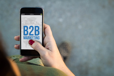 net trade: Top view of woman walking in the street using her mobile phone showing b2b marketing on screen. All screen graphics are made up. Stock Photo