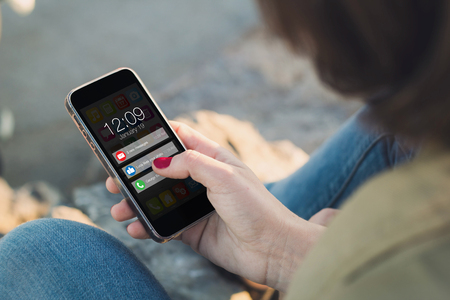 woman holding a smartphone and touching the screen with notifications. All screen graphics are made up.