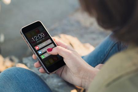 mujer que sostiene un teléfono inteligente y tocando la pantalla con las notificaciones. Todos los gráficos de la pantalla se componen.