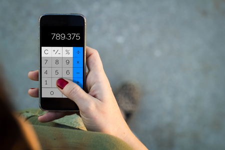 estimating: Top view of woman walking in the street using her mobile phone with calculator app. All screen graphics are made up. Stock Photo