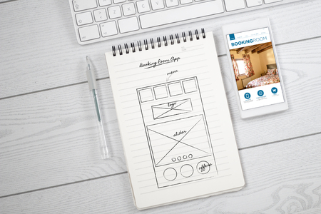 white desktop with notebook and smartphone showing app proyect. All screen graphics are made up.