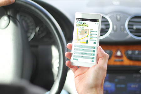 driver holding smartphone with car sharing app interface. All screen graphics are made up. Stockfoto