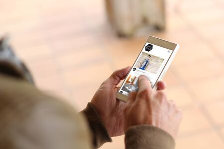 influencer: man touching the screen of his smartphone showing influencer fashion blog. All screen graphics are made up.