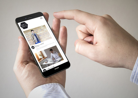 influencer: Close up of man using 3d generated mobile smart phone with influencer fashion model on the screen. Screen graphics are made up. Stock Photo