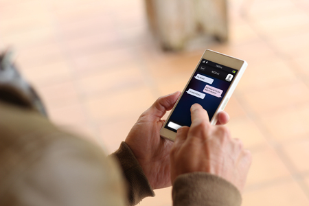man touching the screen of his smartphone showing instant messaging app. All screen graphics are made up.