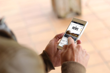 uomo che tocca lo schermo del suo cellulare che mostra sito web di notizie. Tutte le grafiche dello schermo sono costituiti.