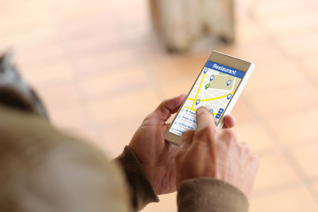 searchbar: man touching the screen of his smartphone at street looking for restaurant. All screen graphics are made up.