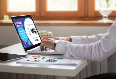 businessman working with laptop at the office. insurance comparator concept. All screen graphics are made up.