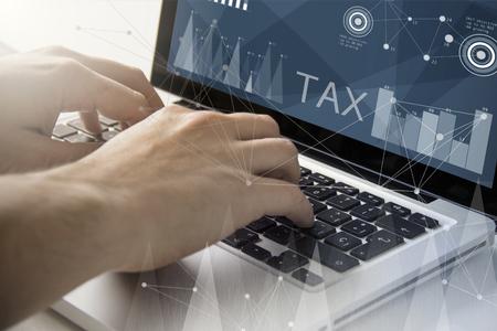 技術とビジネスの概念: 税のソフトウェア画面上でラップトップを使用しての男します。全画面表示のグラフィックスが成っています。
