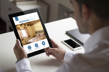 bussinessman: bussinessman at office holding a tablet showing booking room website. All screen graphics are made up.