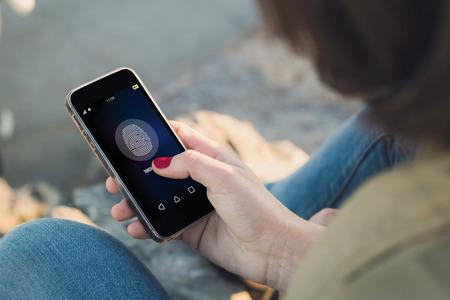 touch: woman holding a smartphone and touching the screen to unlock it. All screen graphics are made up.