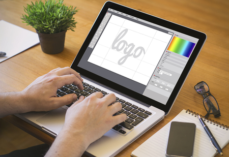 graphic designing: graphic design concept. Close-up top view of a graphic designer designing a icon on laptop. all screen graphics are made up.