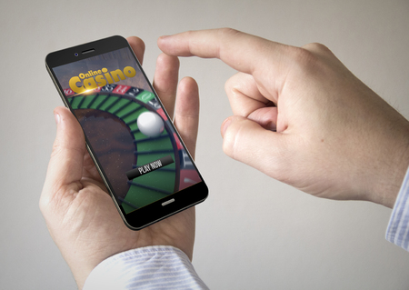 games hand: Close up of man using 3d generated mobile smart phone with online casino on the screen. Screen graphics are made up.