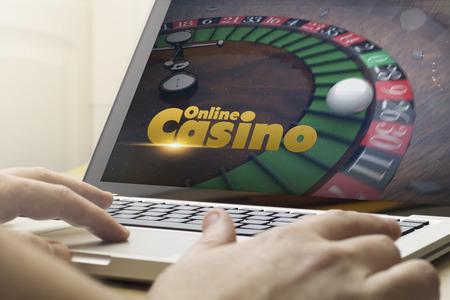 オンライン ゲームのコンセプト: ラップトップを使用して画面上のオンラインのカジノを持つ男します。画面のグラフィックが成っています。 写真素材