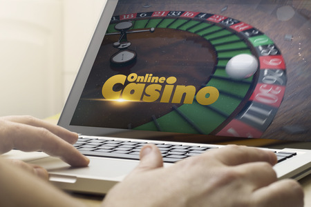 online gaming concept: man using a laptop with online casino on the screen. Screen graphics are made up. Standard-Bild