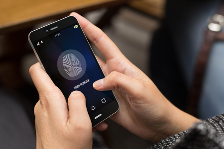 fingerprint: security concept: girl unlocking a digital generated phone. All screen graphics are made up.
