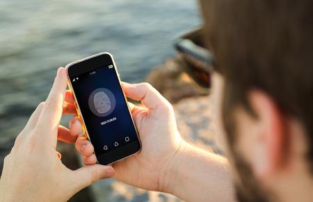 privacidad: el hombre en la costa desbloqueo de su teléfono inteligente. Todos los gráficos de la pantalla se componen. Foto de archivo