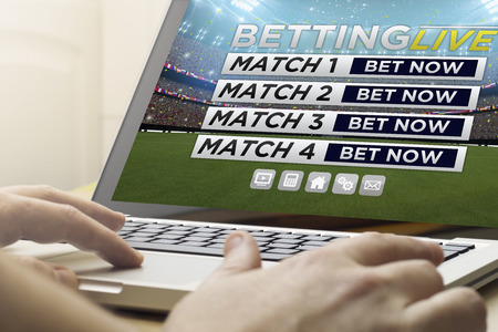 telecommuting: online business concept: man using a laptop with online betting live website on the screen. Screen graphics are made up.