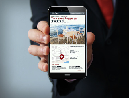 restaurant rating: new technologies business concept: businessman hand holding a 3d generated touch phone with online directory on the screen.