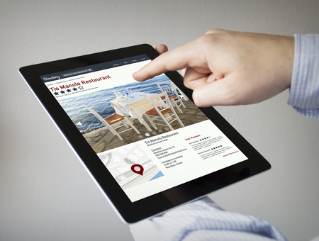 book reviews: new technologies concept: hands with touchscreen tablet with online directory on the screen.