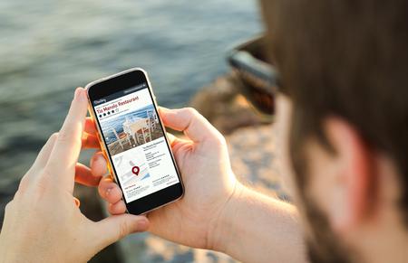 man aan de kust met behulp van zijn smartphone bekijkt online directory. Stockfoto