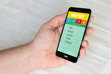 annotation: Close up of hand holding mobile smart phone with notes application on the screen. 3D generated. Stock Photo