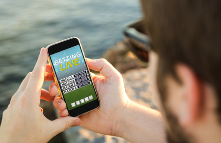 bet: man on the coast using his smartphon to bet onlinee. All screen graphics are made up.