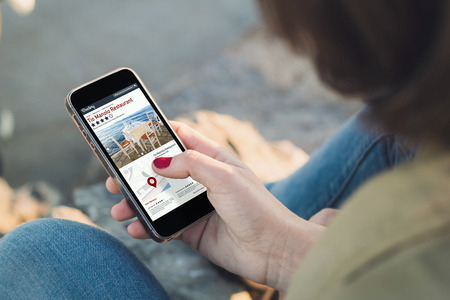 woman holding a smartphone and touching the screen showing online directory. Stock Photo
