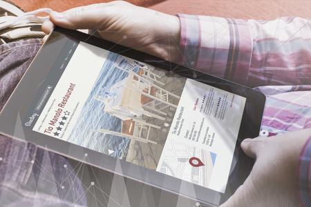 marca libros: vista de primer plano del hombre que sostiene una tableta que muestra el sitio web directorio en línea.