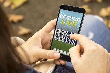 scommesse concetto: donna che tiene un 3d generato smartphone con il sito di scommesse sullo schermo. Archivio Fotografico